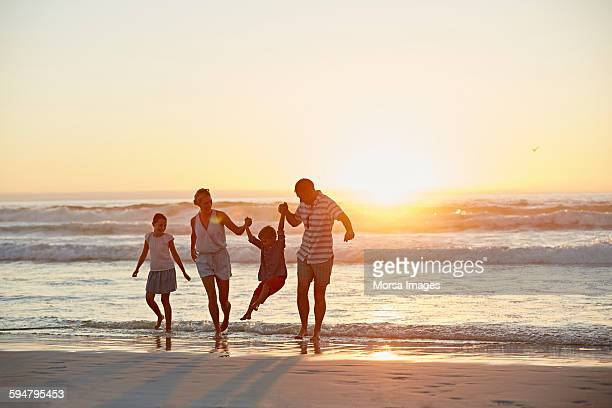 parents with children enjoying vacation on beach - beach stockfoto's en -beelden
