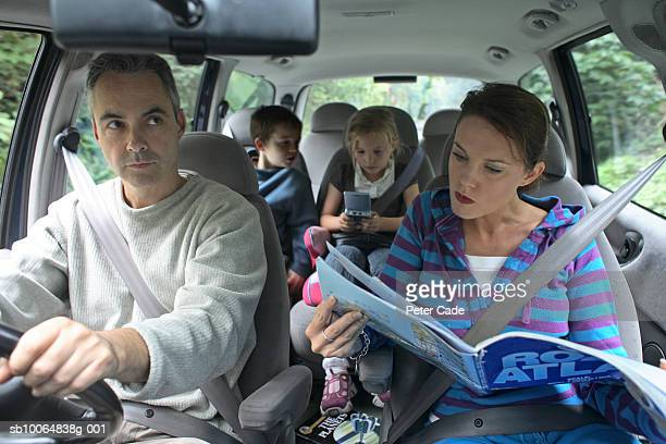Parents with children (6-9) in car, woman looking at map