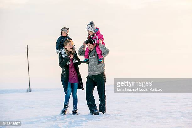 Parents with children in snowy landscape