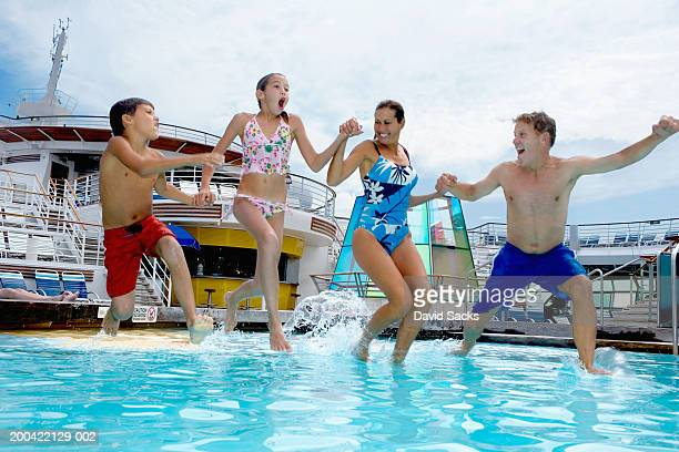 Parents with children (10-12) jumping into pool on cruise ship