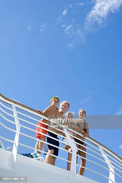 Parents with children (10-12) leaning on rail of cruise ship