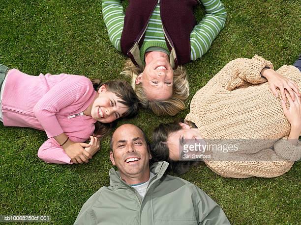 Eltern mit Kinder (8 bis 13) liegen auf Gras, erhöhten Blick auf den Hafen