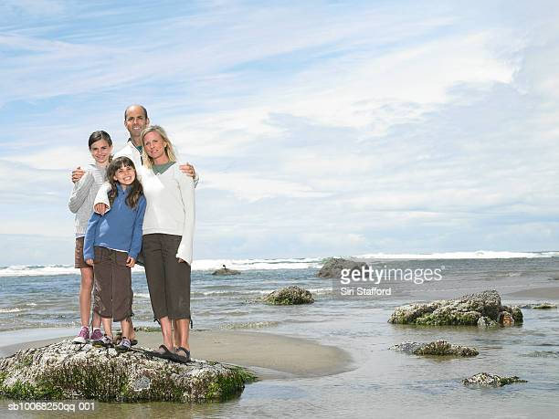 Parents with children (8-13) on beach, smiling, portrait