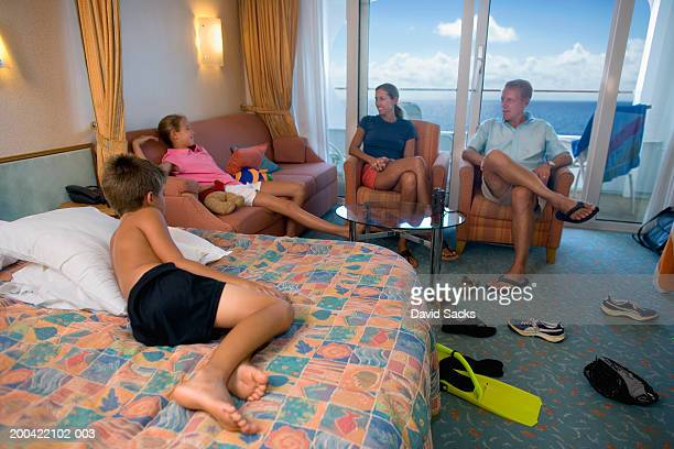 Parents with children (10-12) relaxing in room on cruise ship
