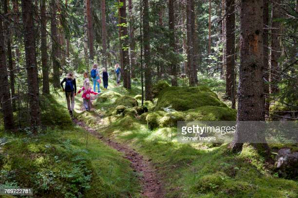 Parents with children walking through forest