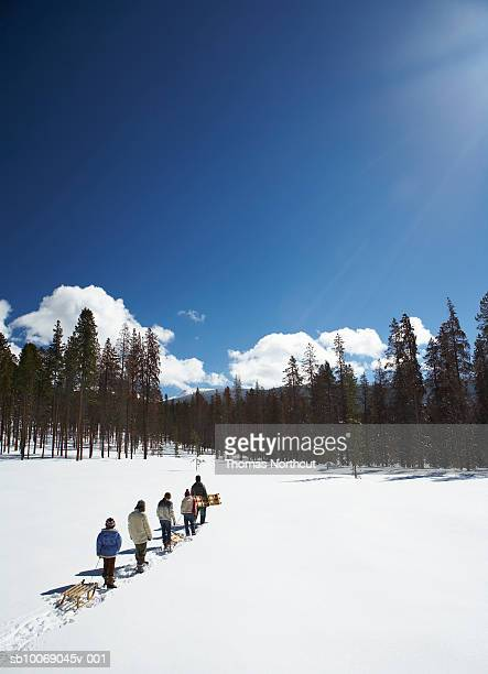 parents with children (8-13) with sled walking in snow - tobogganing stock pictures, royalty-free photos & images