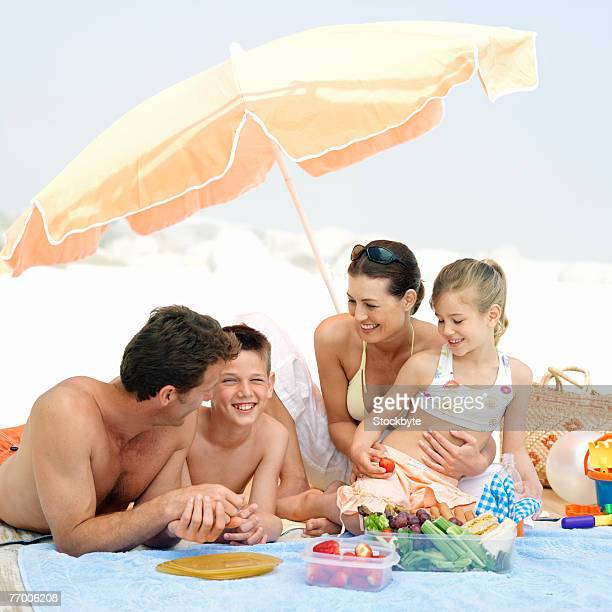 Parents with daughter (8-9 years) and son (12-13 years) eating snacks on beach