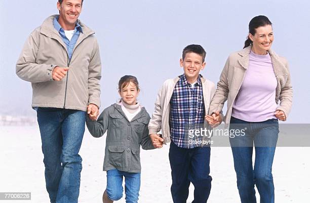 Parents with daughter (8-9 years) and son (12-13 years) running on beach