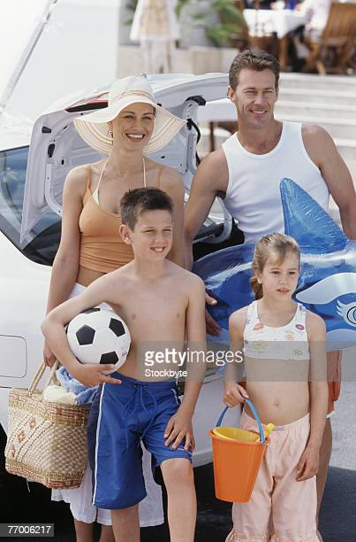 Parents with daughter (8-9 years) and son (12-13 years) standing with beach toys next to car