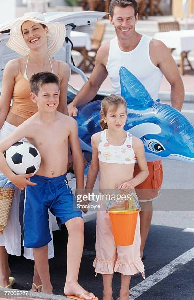 Parents with daughter (8-9 years) and son (12-13 years) standing with beach toys next to car, elevated view