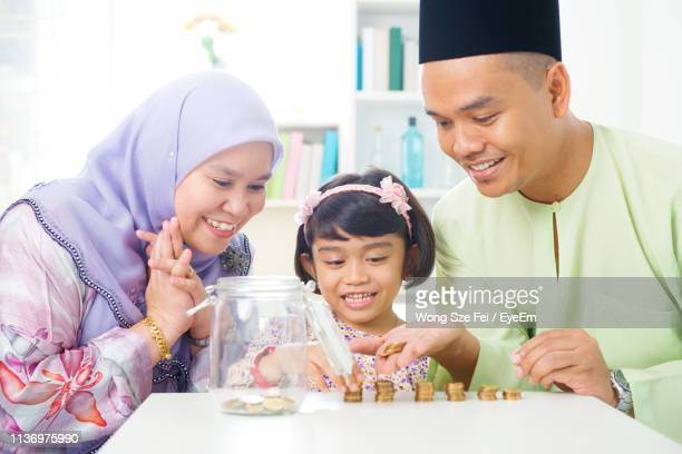 parents with daughter counting coins on table while sitting at home - 40 44 jaar stock pictures, royalty-free photos & images