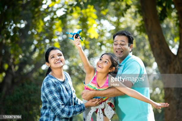 parents with daughter flying toy airplane - indian ethnicity stock pictures, royalty-free photos & images