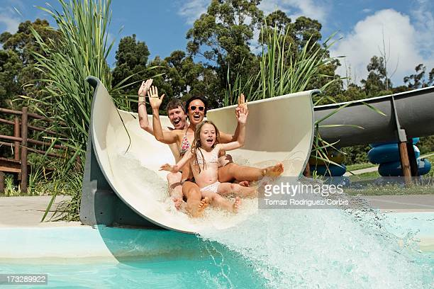 Parents with daughter (6-7) going down water slide