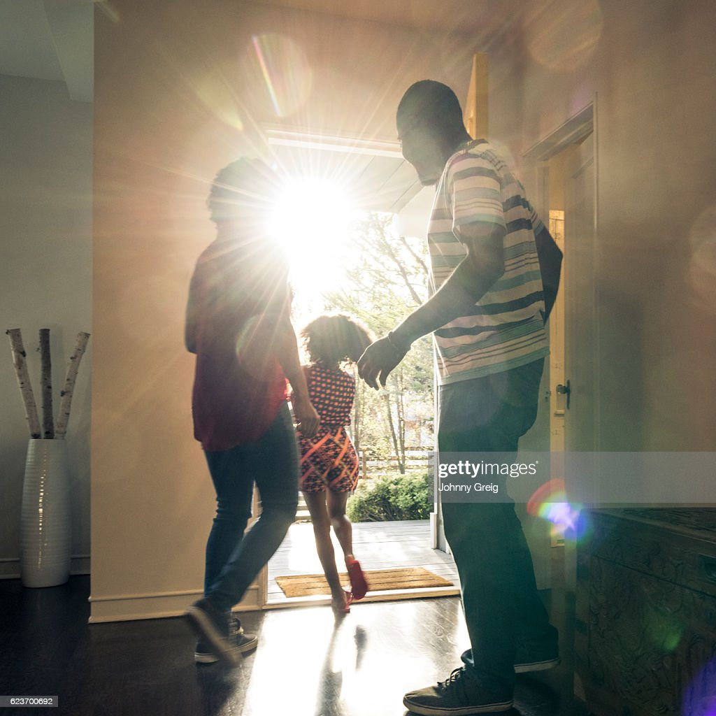 Parents with daughter leaving  the house in bright sunlight : Photo