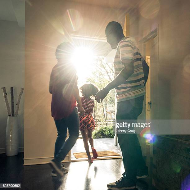 parents with daughter leaving  the house in bright sunlight - dringendheid stockfoto's en -beelden
