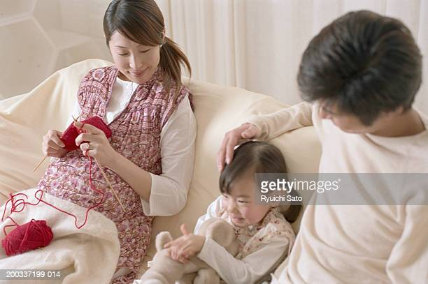 Parents with daughter (4-5) on sofa, woman knitting, elevated view