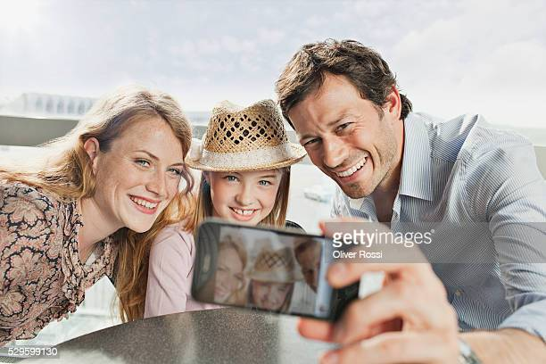 Parents with daughter (5-6) photographing themselves at airport