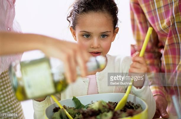 Parents with daughter (6-7) preparing salad, close-up