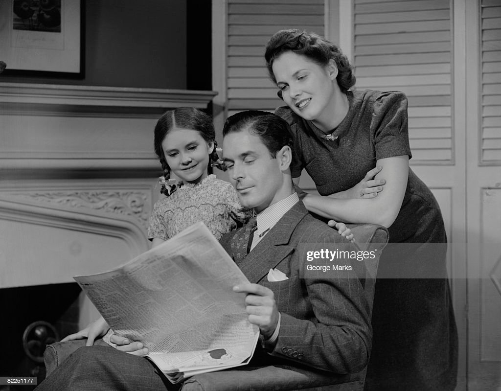 Parents with daughter (6-7 years) reading newspaper together : Stock Photo