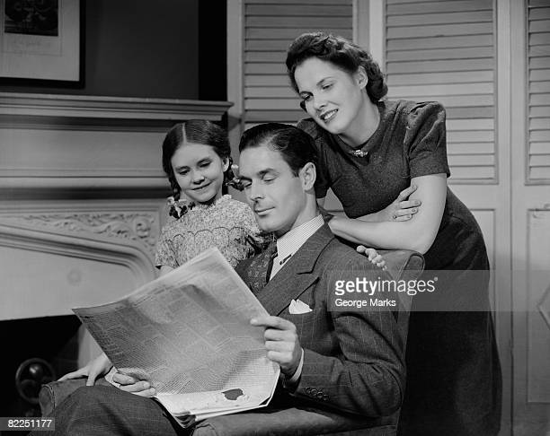 Parents with daughter (6-7 years) reading newspaper together