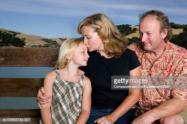 parents with daughter (8-9 years) sitting by wooden balustrade - 8 9 years stock pictures, royalty-free photos & images