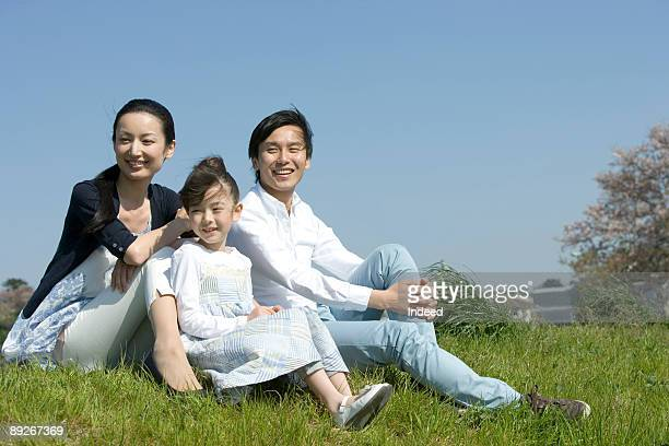 Parents with daughter (8-9) sitting on grass