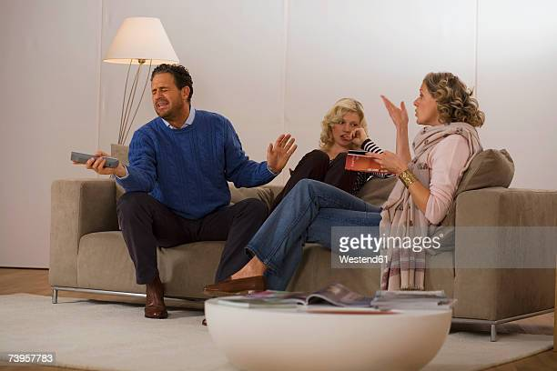 parents with daughter sitting on sofa in living room - arguing stock pictures, royalty-free photos & images