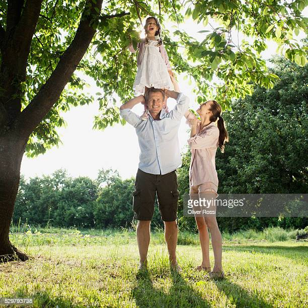 Parents with daughter (5-6) standing on grassy field under tree