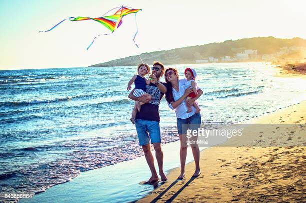 Parents with daughters flying kite together at tropical sunny beach