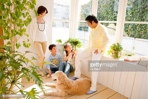 Parents with girl and boy (8-10) talking in room with dog