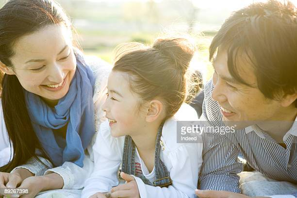 parents with girl (8-9) relaxing on mat - three people ストックフォトと画像