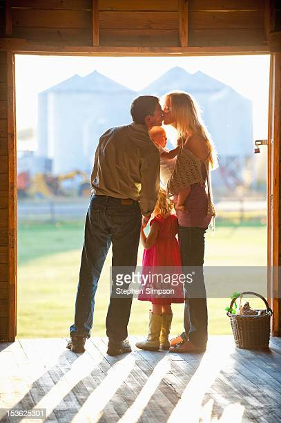 parents with infant kissing in barn doorway
