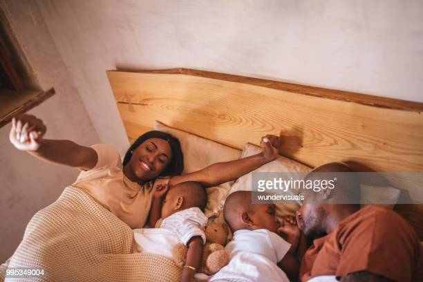 Parents with little children in bed waking up from nap