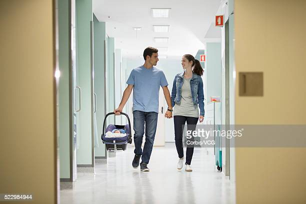 Parents with newborn baby (0-1 months) in hospital corridor