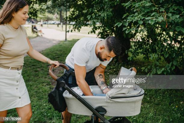 parents with pram in park - carriage stock pictures, royalty-free photos & images