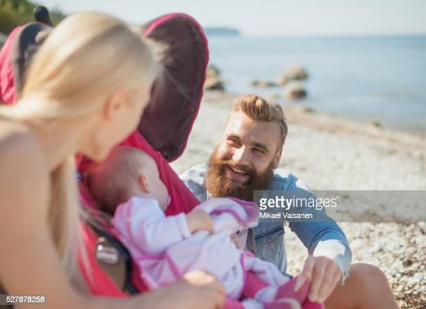 parents with sleeping baby girl (12-23 months) at beach - 12 23 months stock pictures, royalty-free photos & images