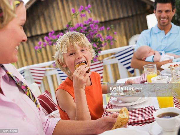 Parents with son (8-9) and baby boy (0-3 months) sitting at breakfast table, smiling