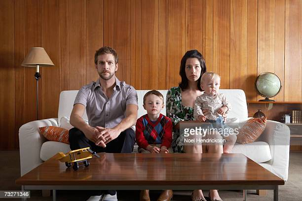 parents with son (3-5), and baby girl (6-9 months) sitting on couch in living room - sofa stock pictures, royalty-free photos & images
