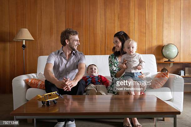 Parents with son (3-5), and baby girl (6-9 months) sitting on couch, in living room