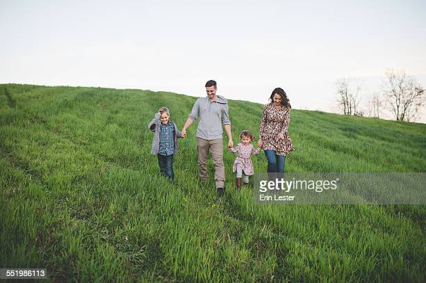 Parents with son and daughter strolling in grassy field