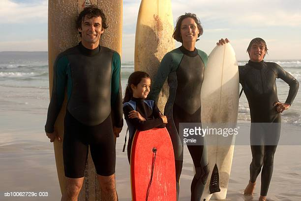Parents with son (14-15) and daughter (6-7) with surfboards on beach