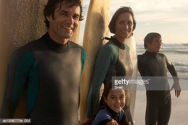 Parents with son (14-15) and daughter (6-7) with surfboards on beach, smiling