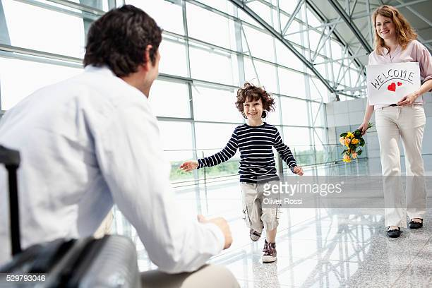 Parents with son (5-6) at airport, boy greeting father