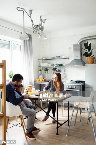 parents with son having breakfast at table in kitchen - simple living stock pictures, royalty-free photos & images