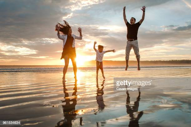 Parents with son jumping at beach against sky during sunset
