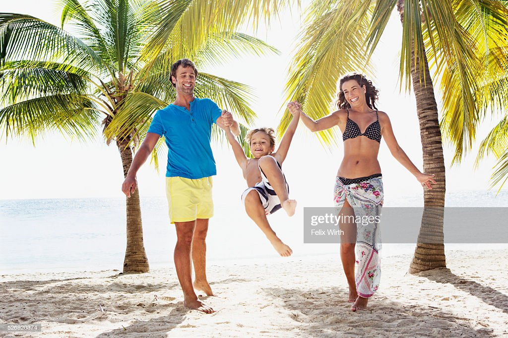 Parents with son (8-9) playing on beach : Stock Photo