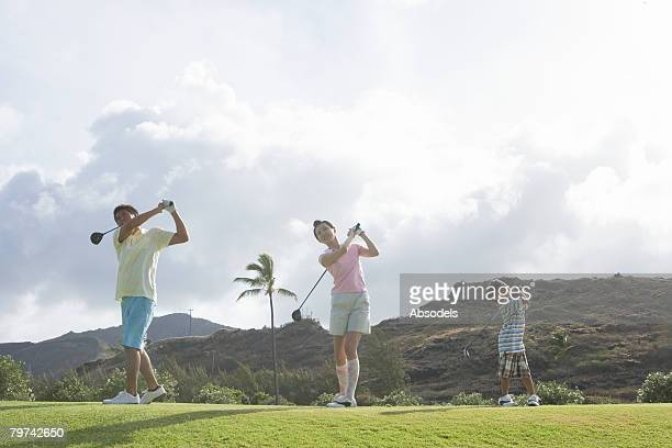 Parents with son (6-7) practicing swing, front view