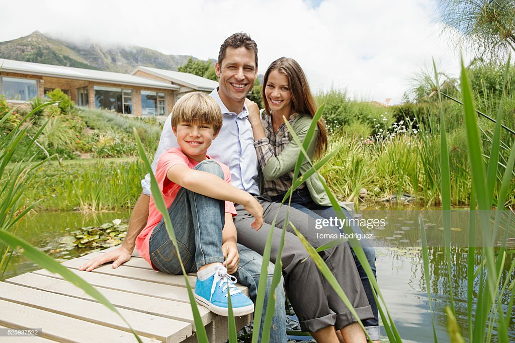 Parents with son (6-7) sitting on pier : Stock Photo