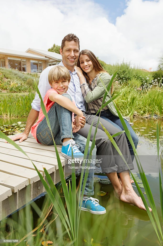 Parents with son (6-7) sitting on pier : Foto stock