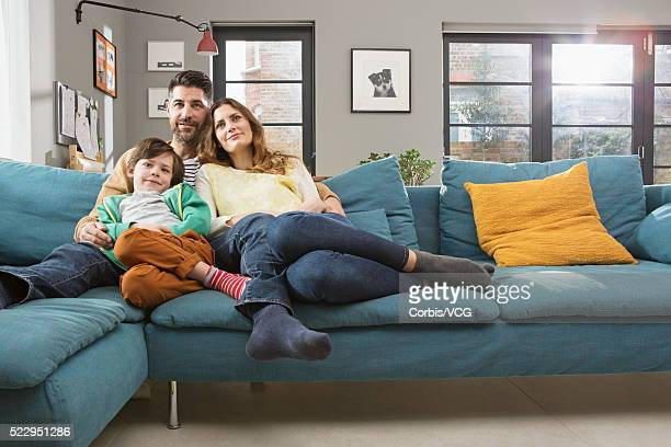 Parents with son (8-9) sitting on sofa